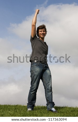 Young man with his arm up - stock photo