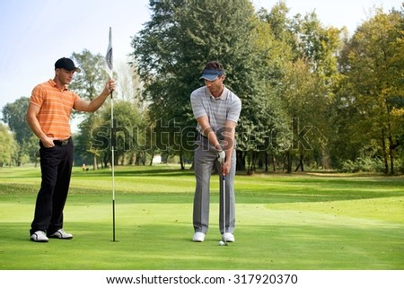 Young man with his friend playing golf in golf course - stock photo