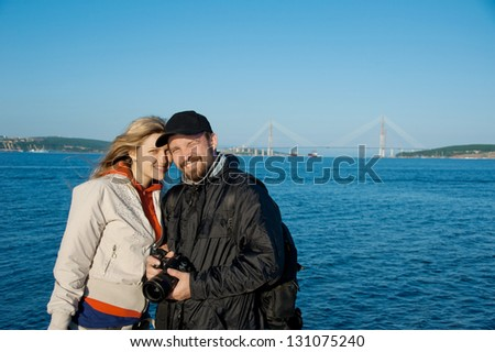 young man with his girlfriend against the background of the bridge