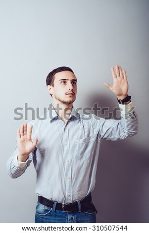 Young man with his hand pressing digitally button in the air - stock photo
