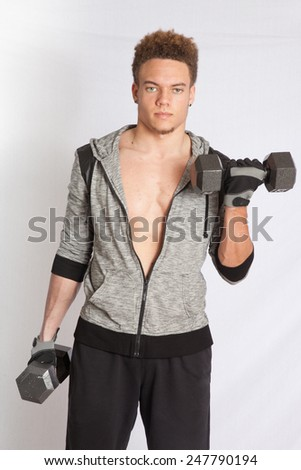 Young man with his jacket open, working out with dumb bells - stock photo