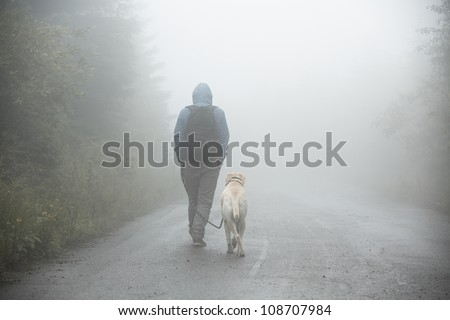 Young man with his labrador on trip in mystery fog. - stock photo