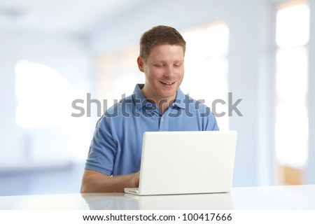 Young man with his laptop computer at his home, smiling