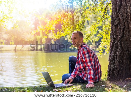 Young man with his laptop in city park outdoor - stock photo