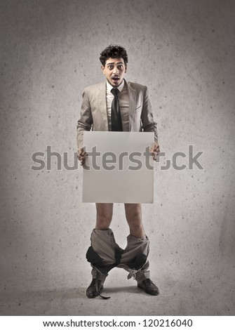 Young man with his pants down covering his private parts with a white cardboard - stock photo