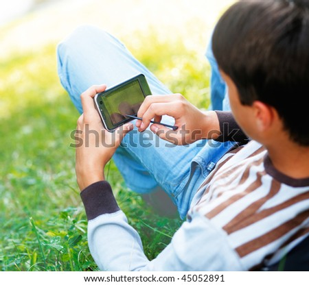 Young man with his pocket computer on a green grass