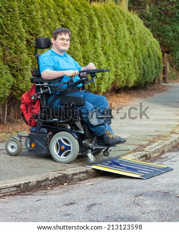 Young man with infantile cerebral palsy caused by birth complications negotiating a mobile ramp on a roadside kerb with his multifunctional wheelchair during a days outing for integration - stock photo