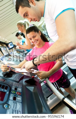 young man with instruction checking his results in gym - stock photo