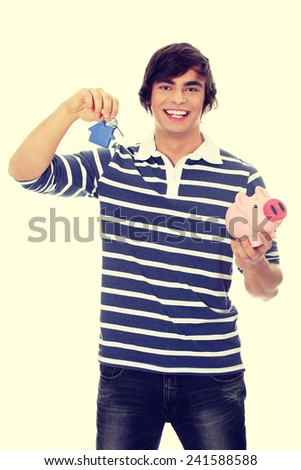 Young man with key and piggybank - stock photo