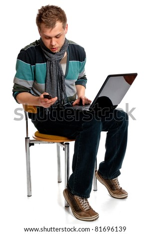 Young man with laptop and cell phone sitting in the studio posing on a white background