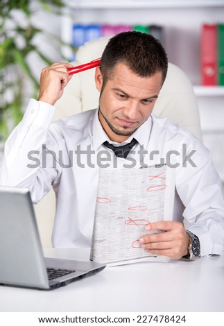 Young man with laptop and newspaper at the table is looking for a job. - stock photo
