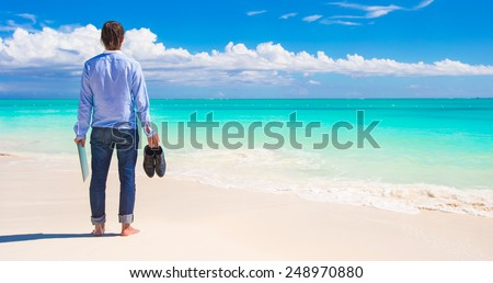 Young man with laptop during tropical beach vacation - stock photo