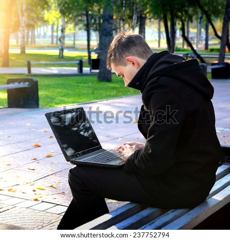 Young Man with Laptop in the Park - stock photo