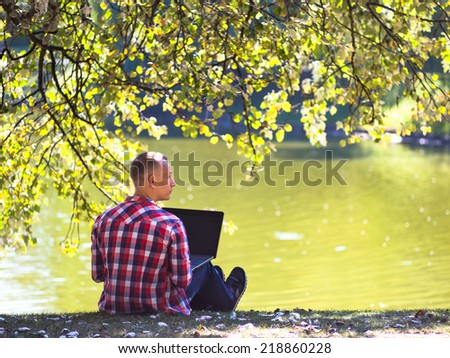 Young man with laptop near lake in city park outdoor  - stock photo