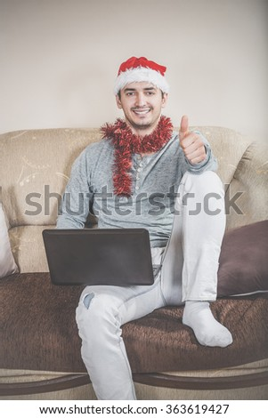 Young man with laptop on a sofa. Businessman with Santa hat working on the computer in New Years eve or day. Male smiling model posing with thumb up. Buying gifts online over internet for loved ones