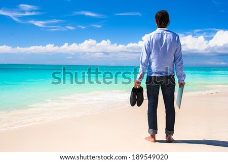 Young man with laptop on the background of turquoise ocean at tropical beach - stock photo