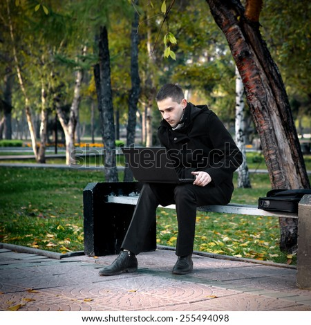 Young Man with Laptop on the bench in the Park - stock photo