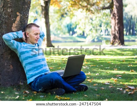 Young man with laptop sitting in green park - stock photo