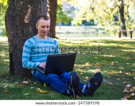Young man with laptop sitting in green park