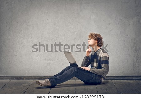 young man with laptop sitting on floor - stock photo