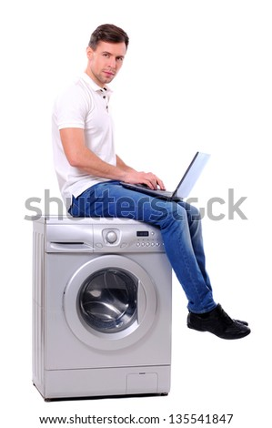young man with laptop sitting on the washing machine