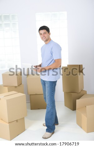 Young man with laptop standing between cardboard boxes. He's looking at camera - stock photo