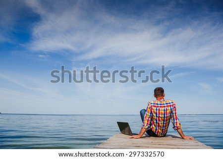 Young man with laptop working outdoor - stock photo