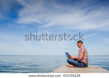 Young man with laptop working outdoor