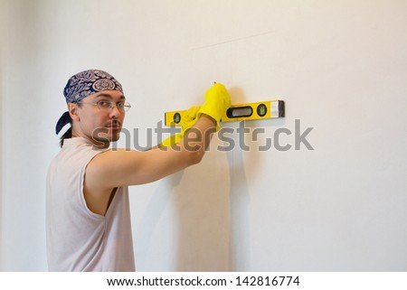 Young man with level working on house renovations - stock photo