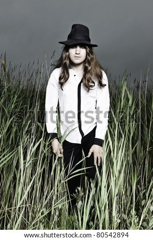 Young man with long brown hair wearing black hat standing in field with long grass. Stormy cloudy sky.
