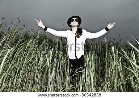 Young man with long brown hair wearing black sunglasses and black hat standing in field with long grass. Stormy cloudy sky.