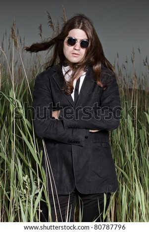 Young man with long brown hair wearing sunglasses and black suit standing in field with long grass. Stormy cloudy sky.