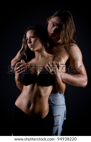 young man with long hair and a muscular back passionately engaged in sex with a beautiful girl - stock photo