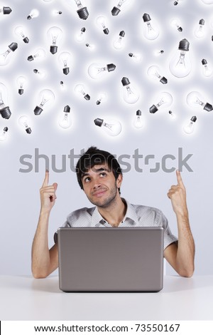 Young man with lots of ideas in the office working with his laptop - stock photo