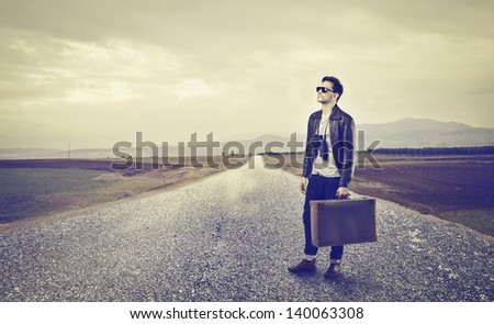 young man with luggage on a desert road - stock photo