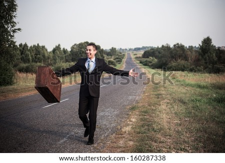 young man with luggage on a road