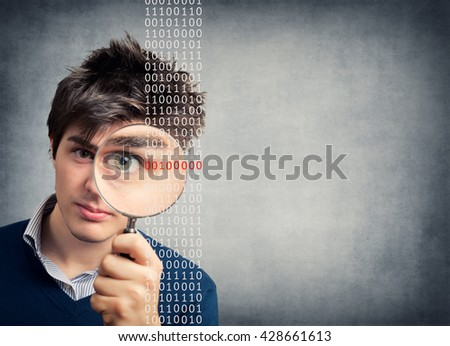 Young Man with magnifying glass looking binary code
