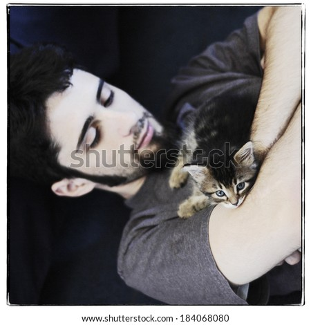 Young man with maine coon kitten, instagram style - stock photo