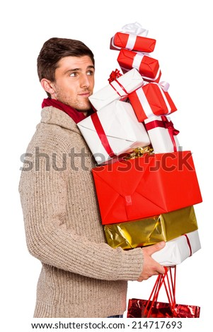 Young man with many christmas presents on white background