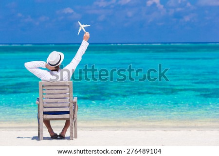 Young man with miniature of an airplane at tropical beach - stock photo