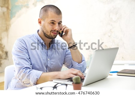 Young man with mobile phone and laptop working in the grunge office