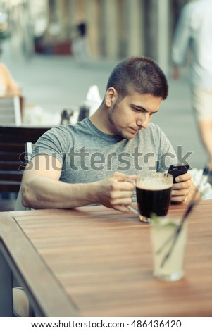 Young man with mobile phone drinking beer in outdoor restaurant