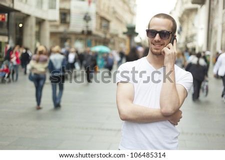 Young Man with mobile phone walking, background is blured city - stock photo