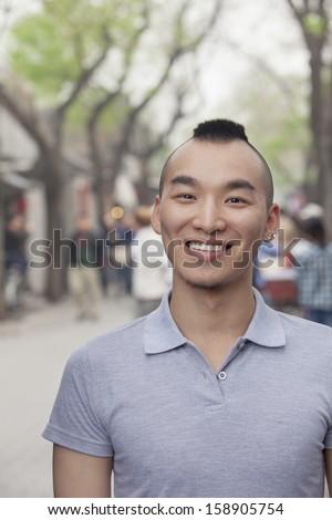 Young man with Mohawk haircut smiling looking at camera - stock photo