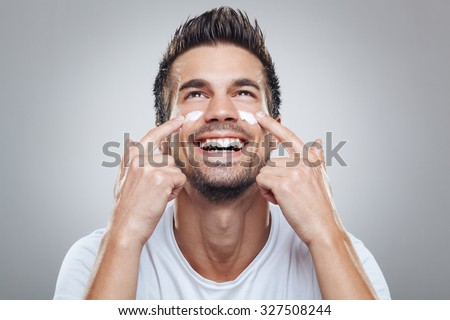 Young man with moisturizer on the face - stock photo