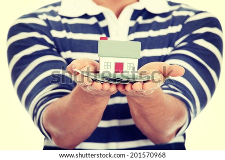 Young man with money and house's model. - stock photo
