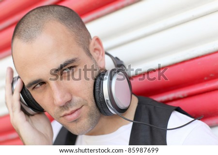 Young man with music headphones - stock photo