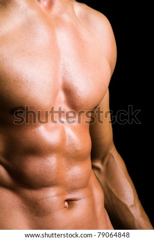 Young man with naked torso on black background - stock photo