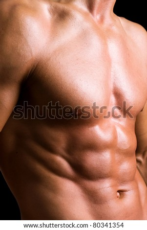Young man with naked torso on black background