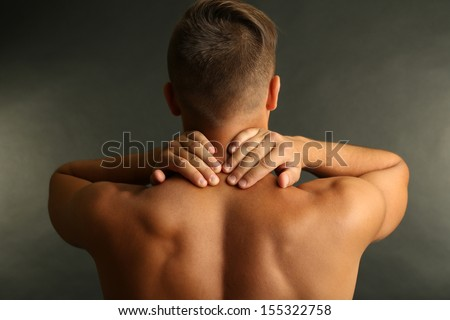 Young man with neck pain on grey background - stock photo